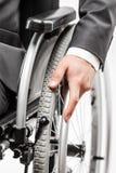 在黑衣服坐的轮椅的无效或残疾商人 免版税图库摄影