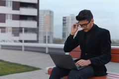 在黑衣服很长时间运转的ablet计算机和疲倦的室外的年轻商人 免版税库存图片