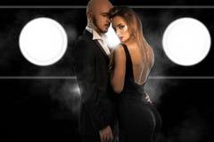 在黑衣服的魅力年轻夫妇在演播室拥抱 免版税库存图片