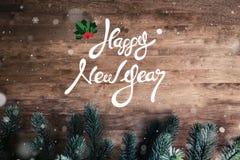 在黑褐色木头背景的新年快乐文本 库存图片