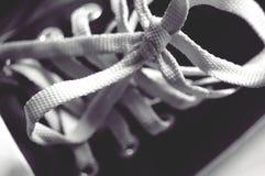 在黑运动鞋的白色鞋带领带穿上鞋子选择聚焦 库存照片