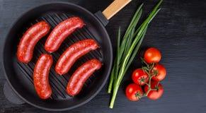 在黑铸铁煎锅的开胃多汁香肠与 免版税库存图片