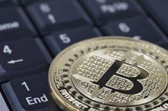 在黑键盘的金黄bitcoin硬币 库存照片