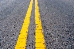在黑高速公路沥青的黄色双重界线 免版税库存照片