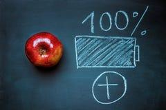 在黑黑板手拉的被充电的电池的红色光滑的苹果计算机 能量Superfood健康饮食概念 素食主义者素食主义者 免版税图库摄影