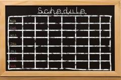 在黑黑板背景的日程表 库存图片