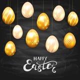 在黑黑板背景的金黄复活节彩蛋 免版税库存照片
