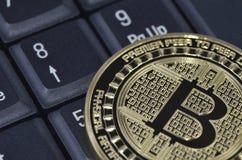 在黑kekyboard的金黄bitcoin硬币 库存照片