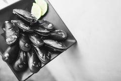 在黑platge,在豪华餐馆的鲜美开胃菜的健康黑白异乎寻常的软体动物食物 免版税库存图片