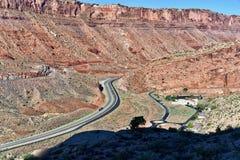 在默阿布,犹他附近的美国高速公路191通过砂岩形成 库存照片
