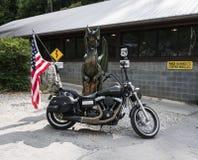 在龙雕象的尾巴的前面哈利戴维森自行车 库存照片