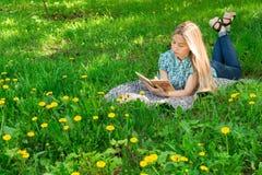 在,认为和写在她的日志的美丽的妇女在与花的草 正面图 免版税图库摄影