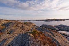 在水上的波浪起伏的岩层 免版税库存照片