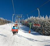 在登上Serak的升降椅下坡滑雪者的 图库摄影