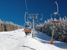 在登上Serak的升降椅下坡滑雪者的 免版税库存图片