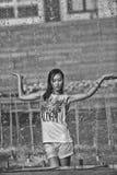 在水下喷气机的快乐的女孩跳舞在城市喷泉的 免版税库存照片