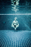 在水下的人在放松的游泳池在莲花positio 免版税库存图片