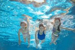 在水下的水池的家庭游泳或的海,母亲和孩子获得乐趣在水中 免版税库存照片