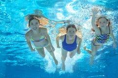 在水下的水池的家庭游泳或的海,母亲和孩子获得乐趣在水中 库存照片