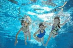 在水下的水池的家庭游泳或的海,母亲和孩子获得乐趣在水中 库存图片