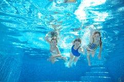 在水下的水池的家庭游泳或的海,母亲和孩子获得乐趣在水中 图库摄影