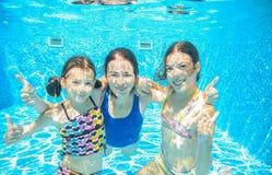 在水下的水池的家庭游泳或的海,母亲和孩子获得乐趣在水中 免版税库存图片