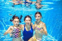 在水下的水池的家庭游泳,母亲和孩子获得乐趣在水中, 免版税库存照片