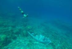 在水下年轻男孩游泳到凹下去的小船 免版税库存照片