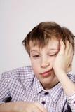 在类不耐烦和疲倦的白肤金发的逗人喜爱的男小学生(乏味)以后 库存照片