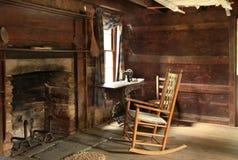 在19世纪修造的老原木小屋黑暗的内部  免版税库存图片