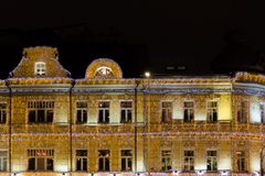 在19世纪大厦的圣诞节照明 用诗歌选装饰的所有墙壁 库存照片
