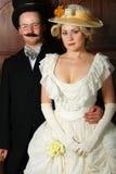 在19世纪服装的夫妇与统治角色的妇女 免版税图库摄影