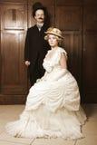 在19世纪服装的夫妇与统治角色的妇女 免版税库存图片