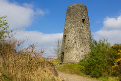 在19世纪领先的一个老风车树桩在背景中开采与现代风轮机翻板在Conlig北爱尔兰 或者 免版税库存照片