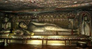 在洞两Viharaya大君的一个大说谎的菩萨雕象Dambulla洞寺庙的 免版税库存图片