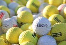 在击中范围的高尔夫球场的白色和黄色实践高尔夫球 库存图片