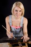 愉快的白肤金发的妇女提供最后一笔给绘在舒适 免版税图库摄影