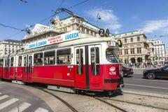 在维也纳国家歌剧院房子前面的人们乘坐路面电车 免版税图库摄影
