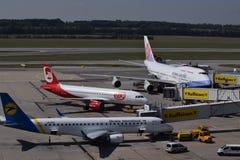 在维也纳机场的终端察觉和中华航空公司波音747-400, Niki空中客车A320乌克兰Internatiol巴西航空工业公司erj190 库存照片
