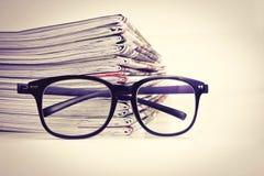 在读书镜片的选择聚焦有堆积的报纸 免版税库存照片