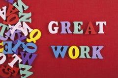 在从五颜六色的abc字母表块木信件组成的红色背景,广告文本的拷贝空间的了不起的工作词 免版税库存照片