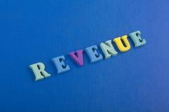 在从五颜六色的abc字母表块木信件组成的蓝色背景,广告文本的拷贝空间的收支词 免版税库存图片