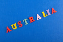 在从五颜六色的abc字母表块木信件组成的蓝色背景,广告文本的拷贝空间的澳大利亚词 库存图片