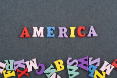 在从五颜六色的abc字母表块木信件组成的黑委员会背景,广告文本的拷贝空间的美国词 库存图片