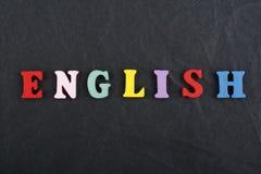 在从五颜六色的abc字母表块木信件组成的黑委员会背景,广告文本的拷贝空间的英国词 库存图片