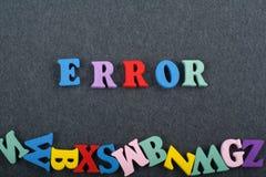 在从五颜六色的abc字母表块木信件组成的黑委员会背景,广告文本的拷贝空间的错误词 库存照片