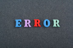 在从五颜六色的abc字母表块木信件组成的黑委员会背景,广告文本的拷贝空间的错误词 免版税库存图片