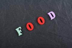 在从五颜六色的abc字母表块木信件组成的黑委员会背景,广告文本的拷贝空间的食物词 库存照片