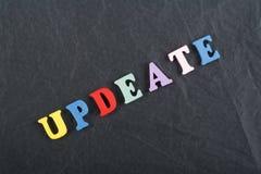 在从五颜六色的abc字母表块木信件组成的黑委员会背景,广告文本的拷贝空间的UPDEATE词 免版税库存照片