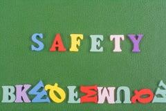 在从五颜六色的abc字母表块木信件组成的绿色背景,广告文本的拷贝空间的安全词 免版税库存照片